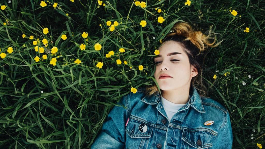 nő sárga virágok közt fekszik