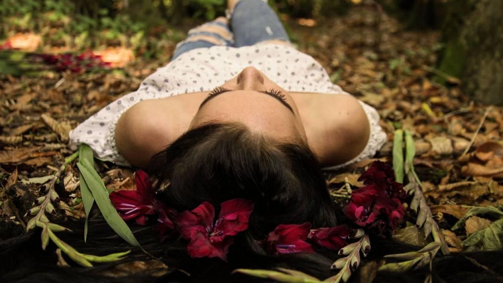 erdőben virágok közt fekvő nő