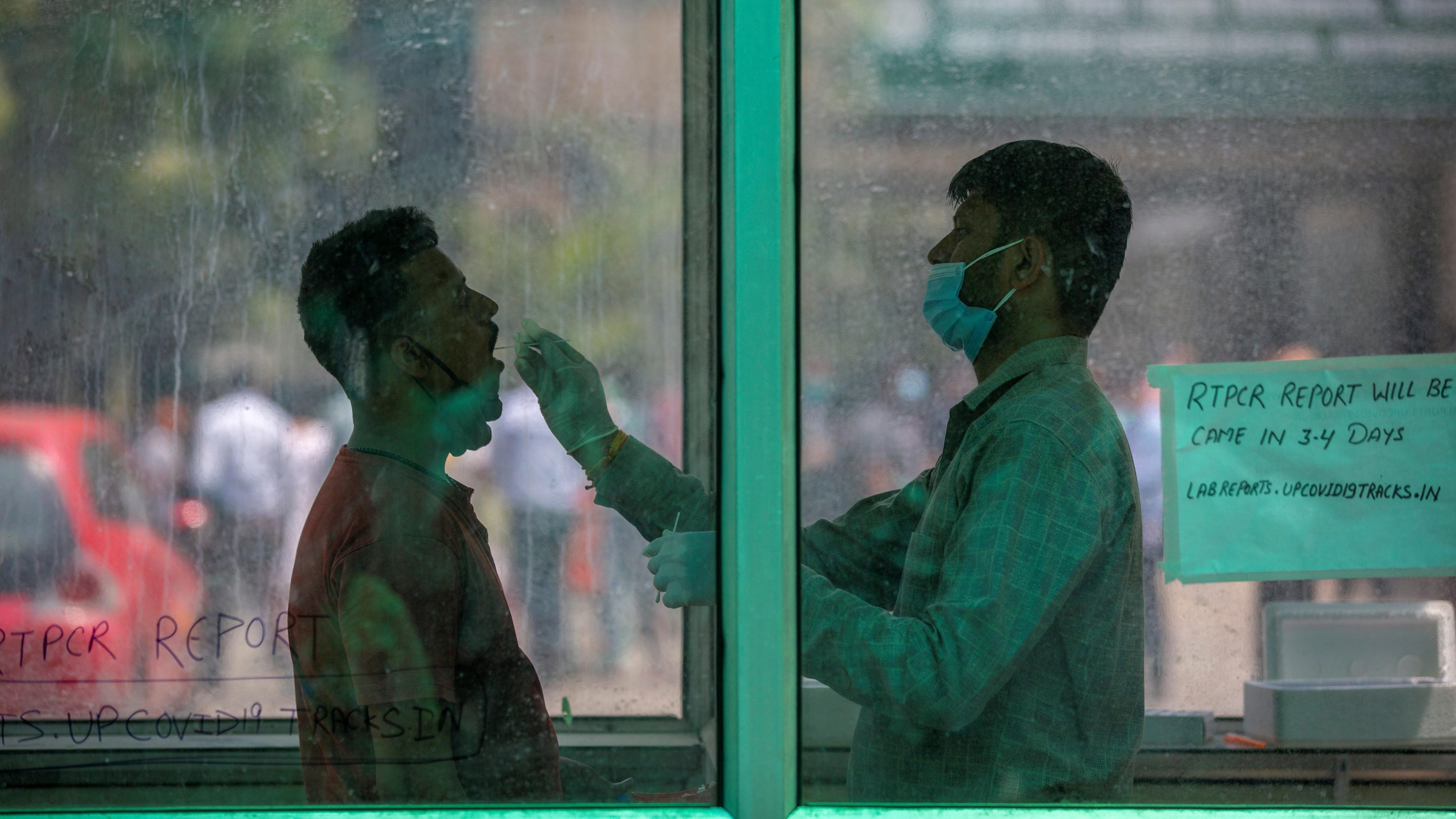 Vizsgálati mintát vesznek koronavírus-tesztre egy férfitől az Újdelhi szomszédságában fekvő Noidában 2021. április 15-én.