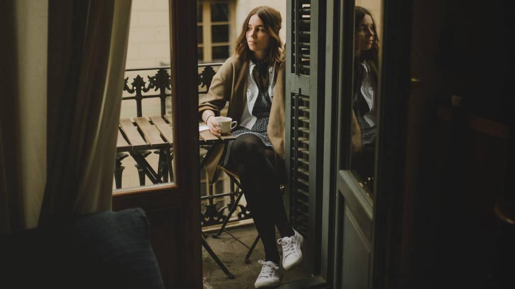 szomorű nő erkélyen kávézik