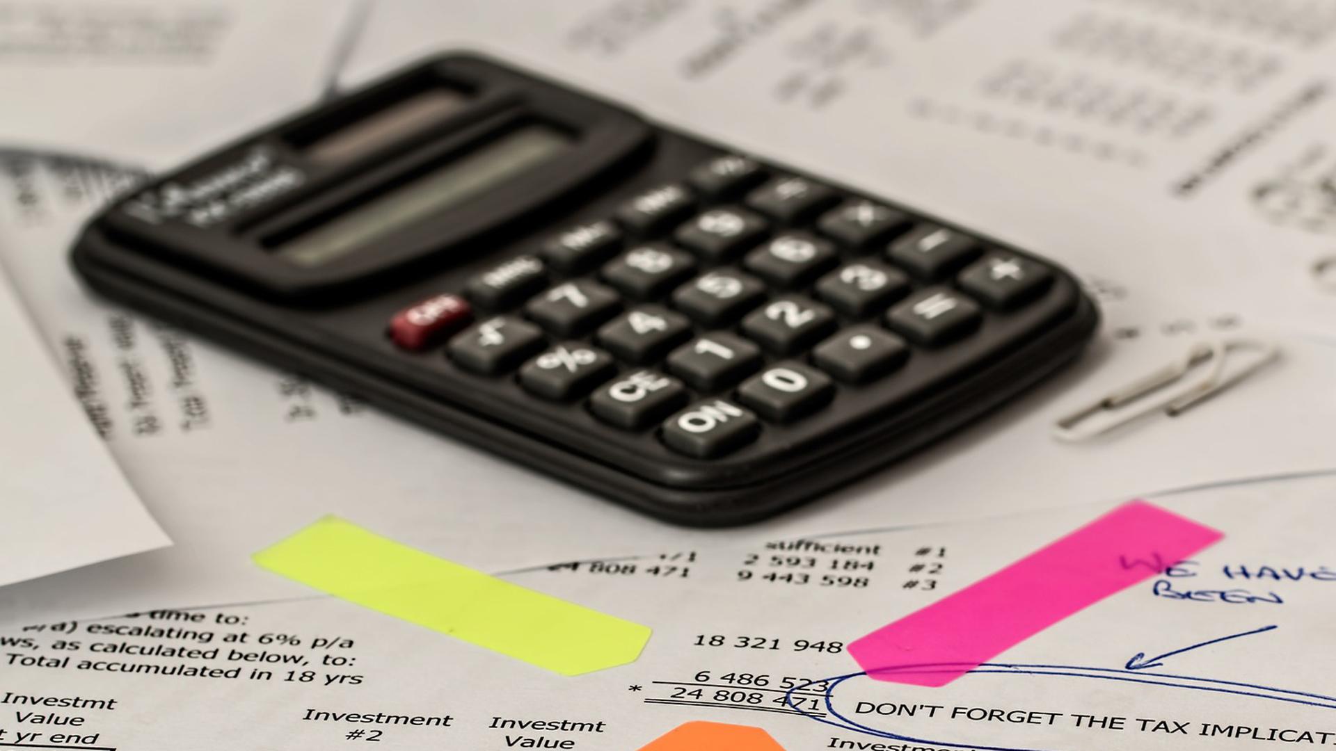 számológép fekszik a papíralapú adóbevalláson