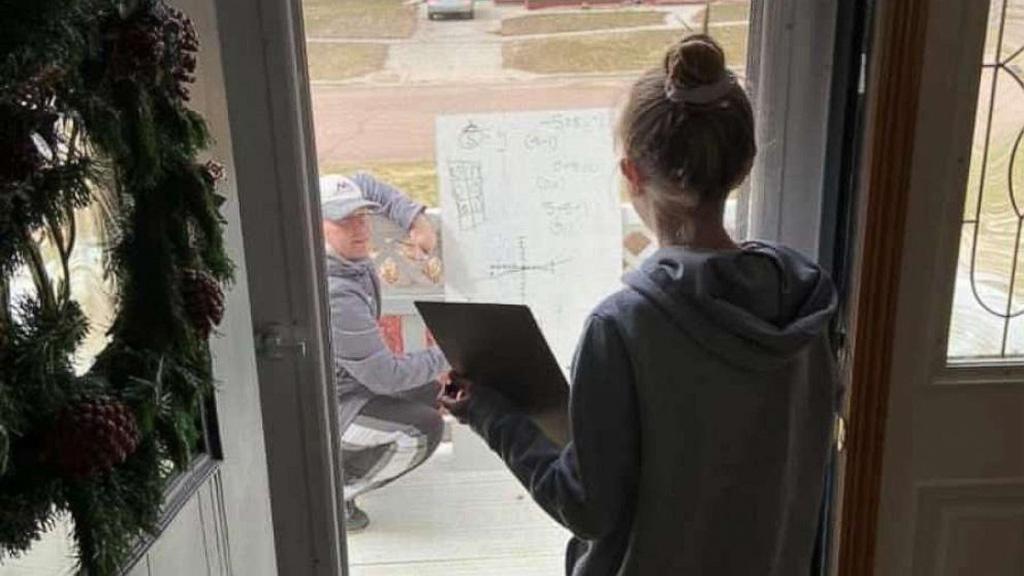 A diákja ajtaja előtt órát adó matektanár