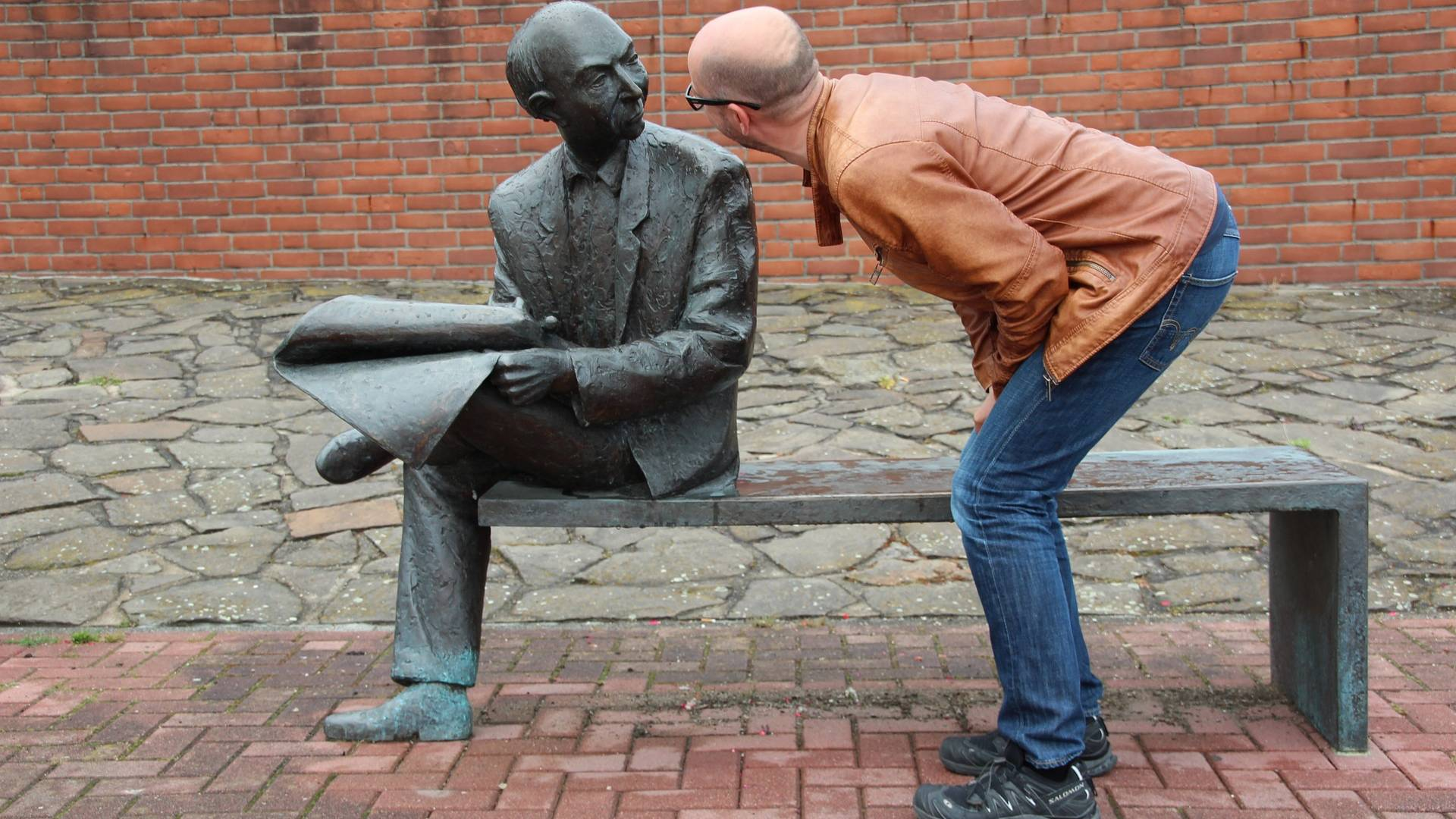 szobor arcába néző férfi