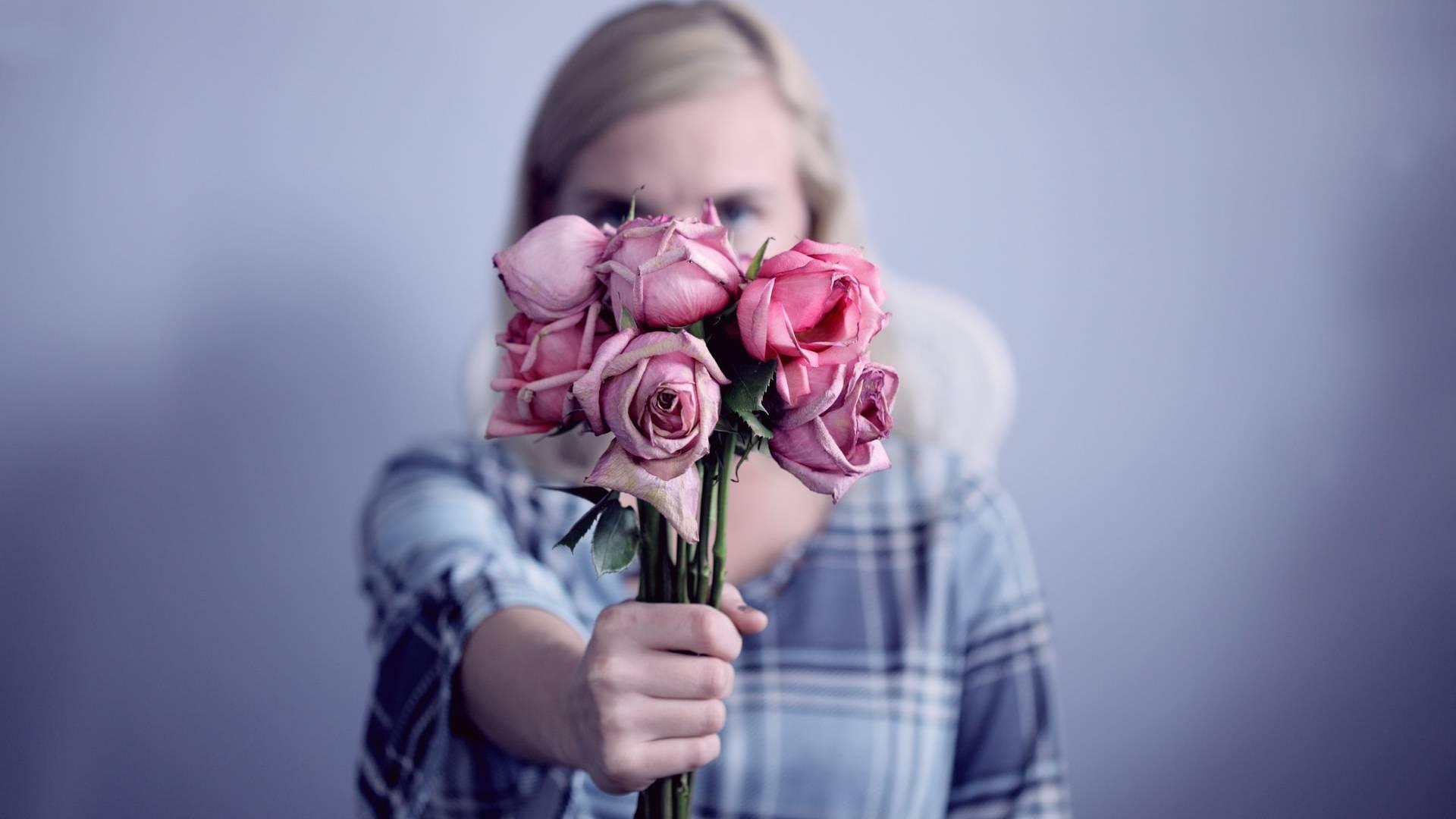 mérges nő hervadt rózsacsokorral