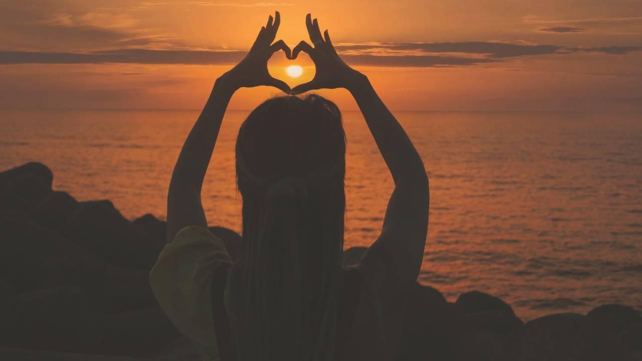 nő naplementében szívet mutat