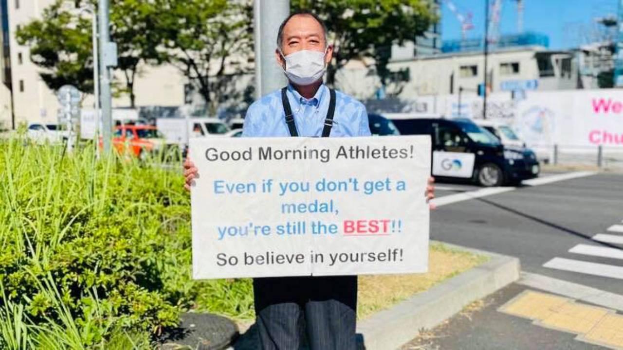 Ez a táblát tartó férfi a tokiói olimpia titkos csillaga