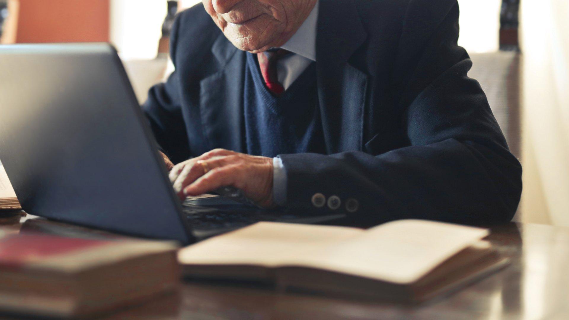 Nyugdíjas férfi a laptop előtt